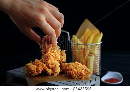 Hand Grabs Crispy Kentucky Fried Chicken. French Fries And Tomato On Black Wooden Table