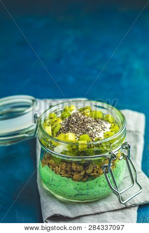 Chia Seed Pudding With Matcha Green Tea, Kiwi And Granola In Glass On Dark Blue Concrete Background.