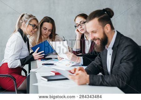 Idle Employee. Team Member Slacking Off. Smiling Man Browsing Tablet At Workplace.