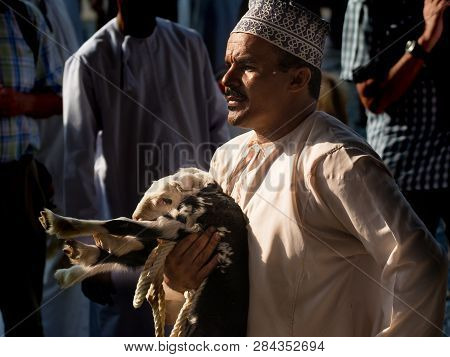 Nizwa, Oman - November 2, 2018: Omani Man Holds A Goat In The Nizwa Animal Market