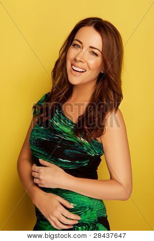 Carefree Laughing Woman In Green Dress, beautiful redhead woman laughing merrily in a green formal dress, studio on yellow.