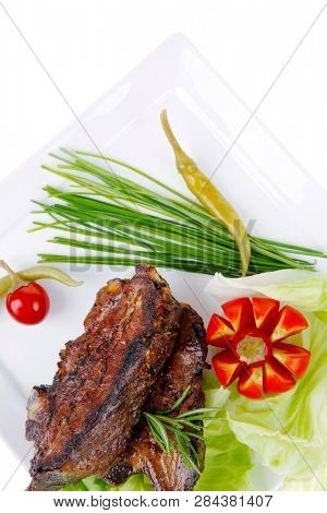meat savory: roast ribs on white plate with peppers lettuce tomato and chives over white background