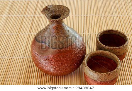 Sake bottle and two cups on a bamboo mat
