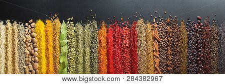 Spices And Herbs For Website Headers. Seasoning Scattered On Black Table, Background For Packing Wit