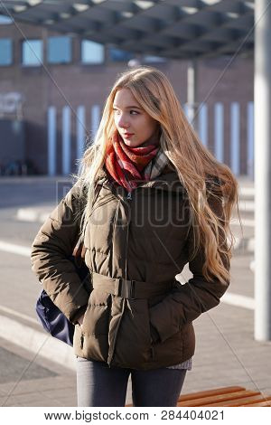 Candid Street Style Image Of Young Woman Waiting At Bus Station On A Sunny Day In Winter