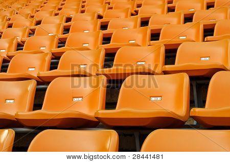 Orange Empty Plastic Seats At Stadium