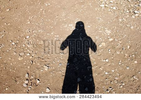 Dark Shadow Of The Photographer On The Stone Surface Background Of The Ground Or Photographer Taking