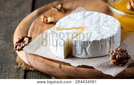 Brie Type Of Cheese. Camembert Cheese. Fresh Brie Cheese And A Slice On A Wooden Board With Nuts, Ho