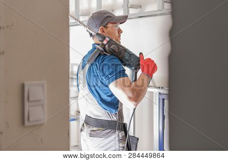 Caucasian Construction Worker With Heavy Duty Drill Driver. Industrial Theme.