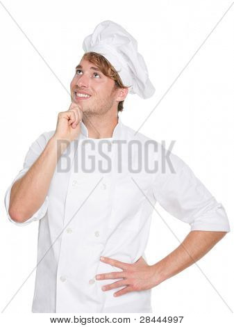 Thinking chef, baker or male cook. Young man in chefs whites uniform smiling happy looking up. Portrait of young chef in his twenties.