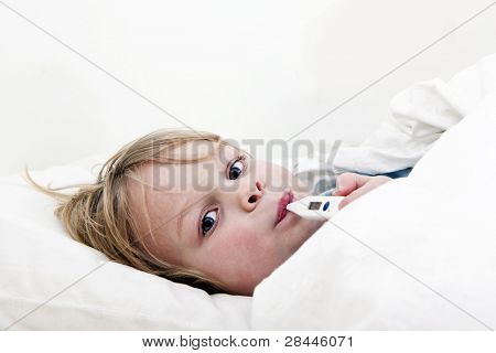 Ill young child, lying in bed with a thermomether, measuring the height of his fever and looking into the camera