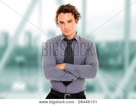 Closeup of a young business man arms crossed standing in a light and mordern business hall.