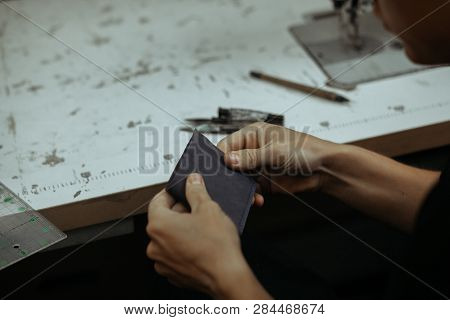 Leather Goods Master Hands And Handmade Leather Wallet. Crafting Tools Lay On Table. Workflow In The