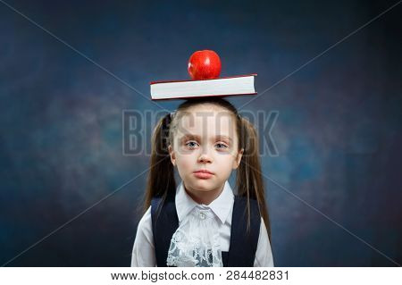 Cute Schoolgirl Hold Book Apple on Head Portrait. Calm Adorable Young Girl with two Ponytail Look at Camera on Dark Background. Elementary School Child Balance Textbook with no Emotion poster