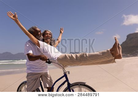 Side view of happy senior man rides a bicycle with senior woman sitting on handlebar at beach in the sunshine with mountains in the background