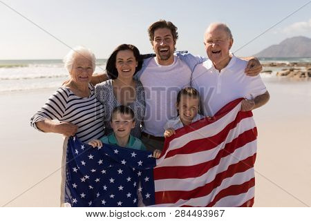 Front view of happy multi-generation family with american flag standing on beach in the sunshine