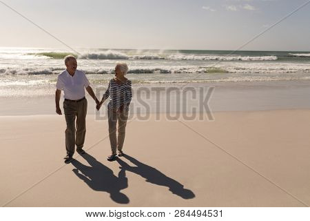 Front view of happy senior couple holding hands and walking on beach  in the sunshine