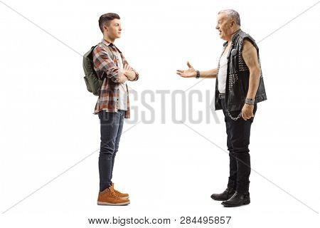 Full length profile shot of an elderly male punker talking to a young teenage male student isolated on white background