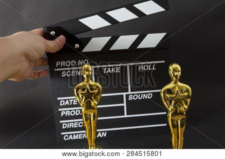 Xalapa, Veracruz, Mexico- February 14, 2019: Hand Holding A Clapboard And Two Plastic Oscar Awards A