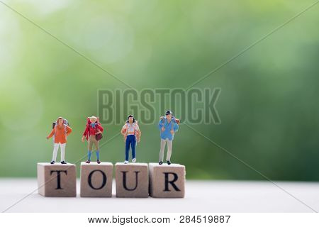 Group Miniature Traveler And Hiker Backpack Standing On Wooden Text Tour For The Tourist And Adventu