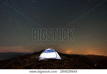 Tourist Camping At Summer Night On The Top Of Rocky Mountain. Glowing Tent Under Amazing Night Sky F