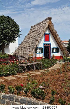 Classical small house  on Madiera. A bright red door, a straw triangular roof, a small front garden and an accurate stone path