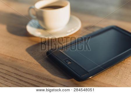 Selective Focus Of Ebook Near Cup With Drink On Table