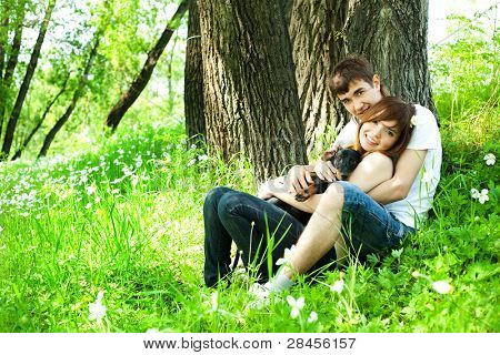 happy young couple spending time in summer park with their puppy