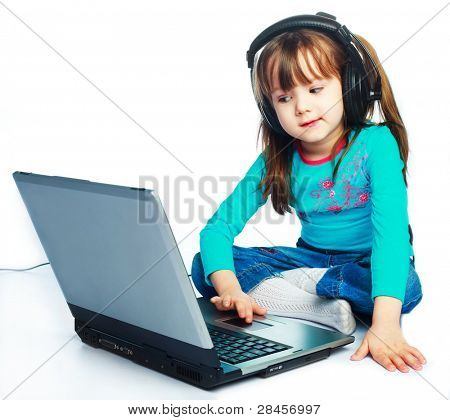 cute smiling little girl wearing earphones with a laptop on the floor