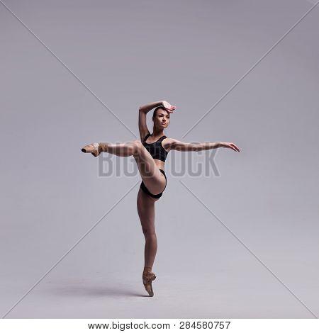 Beautiful Ballet Dancer Posing On Pointes. Ballerina Wearing Black Swimsuit Isolated On Light Grey S