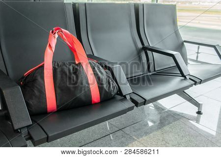 Suspicious Black Sport Bag Left On Chairs Unattended. Lost Luggage. Concept Of Safety In Public Plac