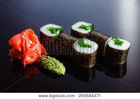 Sushi Rolls Maki With Chuk Algae On A Black Background. Traditional Japanese Cuisine (close)