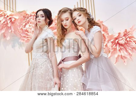 Beautiful Trio Brides In Expensive Wedding Dress In Presence Of Large Artificial Flowers. Three Girl