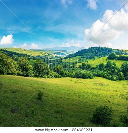 Beautiful Countryside Summer Landscape. Forested Rolling Hill With Grassy Meadow. Village In The Val
