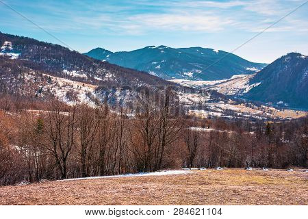Early Springtime In Mountainous Countryside. Village In The Valley. Leafless Trees On The Meadow Wit
