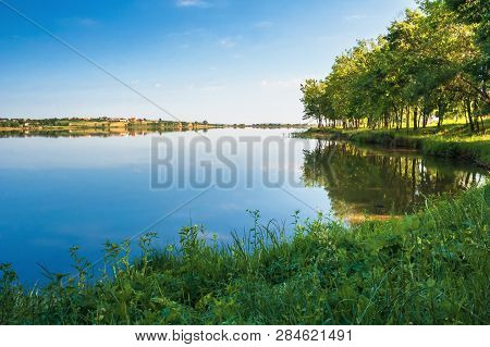 Beautiful Summer Scenery Near The Lake. Trees On The Grassy Shore In Morning Light. Village On The O