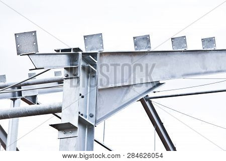 Part of the building structure of galvanized parts. Galvanized parts on a construction site in rainy weather. Waiting for the installation of metal structures. Galvanized metal does not corrode. poster