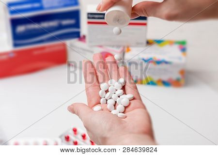 A Pharmacist Is Pouring A Pile Of Medicine On Her Hand