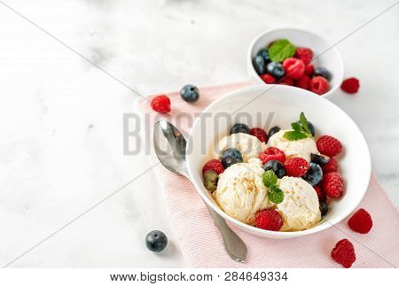 Close Up Of Vanilla Ice Cream With Berries On White Table
