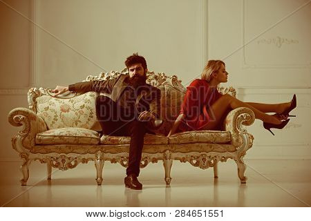 Fashion Couple On Sofa. Fashion Shoes For Woman At Bearded Man. Business Fashion And Formal Wear For