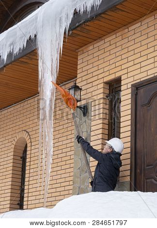 Janitor eliminates frost from the roof with a shovel. poster