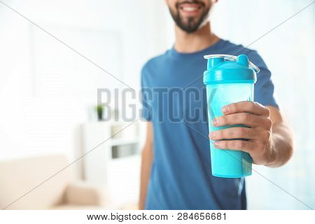 Young Man With Bottle Of Protein Shake At Home, Closeup. Space For Text