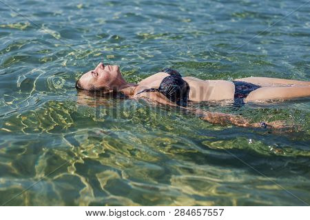 Woman On Holiday Relaxed Floating On Water