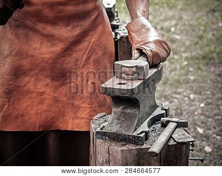 . Blacksmith Hand With A Hammer On Steel Anvil . Hand Of A Blacksmith In Leather Gloves With Hammer