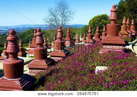 February 10, 2019 In Whittier, Ca:  Manicured Plants And Flowers Surrounding Buddhist Headstones On