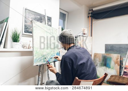 Back Of A Creative Man Painting A Picture Of Oil In A Home Studio. Painter Sits At Home With Brushes
