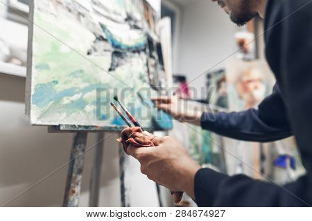Professional Artist Paints Oil Painting On Canvas, Hands With Brushes Close Up And In Focus. Creativ