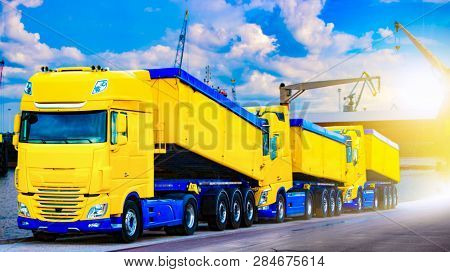 On The Road A Car For Transportation Of Grain . The Yellow Truck With The Trailer . Agricultural Sil
