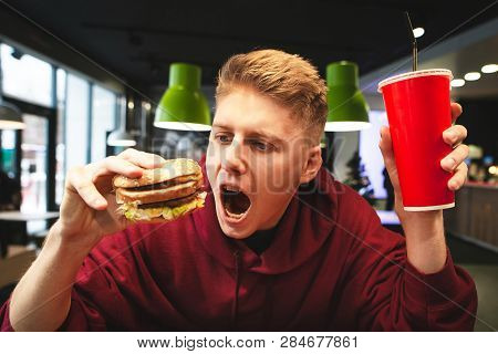 Portrait Of An Emotional Young Man Holding A Glass Of Beverage And A Burger, Looking At A Burger And