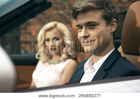 Beautiful Young Married Couple Sitting In Cabrio Car
